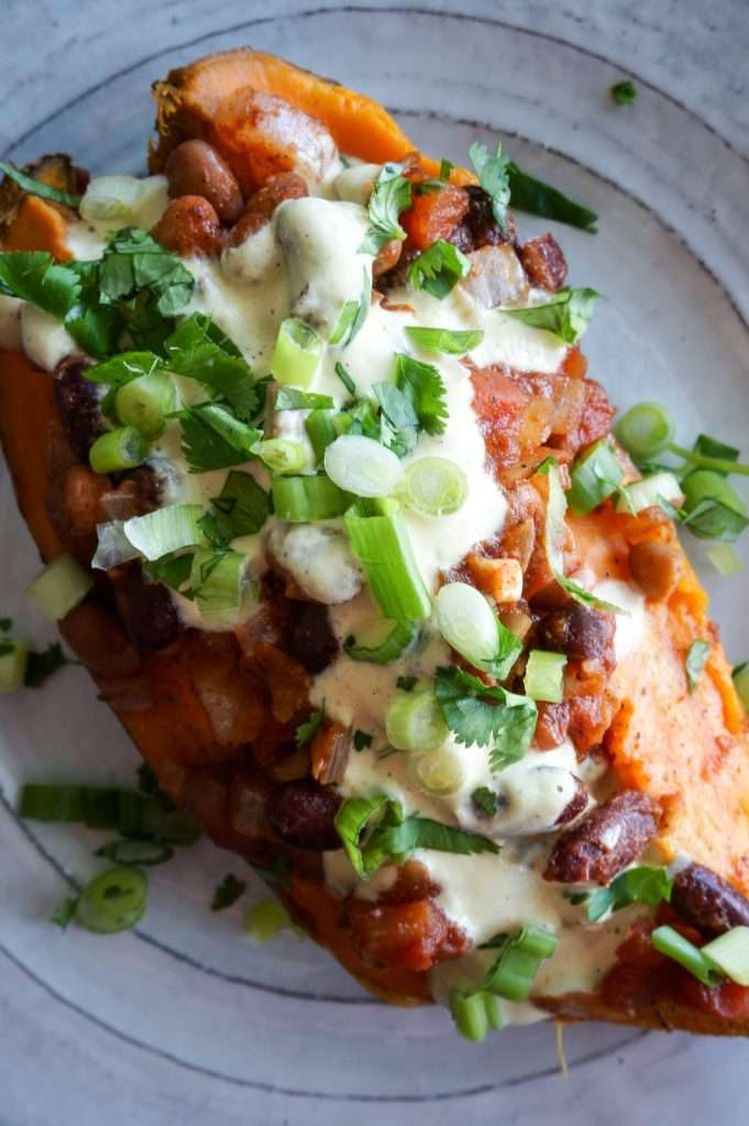 Close up overhead of vegan stuffed sweet potato on white plate.